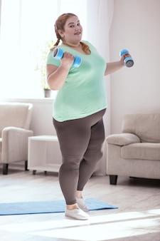 Ejercicio principal. mujer pelirroja regordeta de pie junto a la estera de yoga mientras hace ejercicios con pesas
