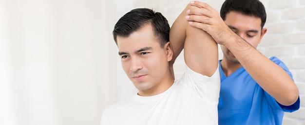 Ejercicio de rehabilitación de entrenamiento del terapeuta, estiramiento de tríceps en la cabeza, a un paciente masculino en el hospital