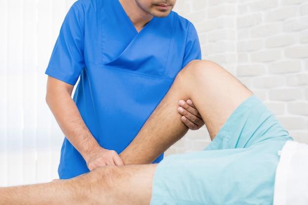 Ejercicio de rehabilitación de fisioterapeuta para paciente con pierna rota