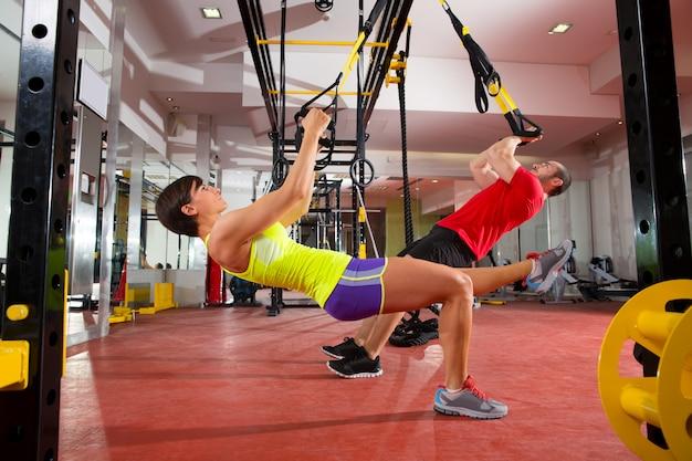 Ejercicios de entrenamiento de fitness trx en gimnasio mujer y hombre