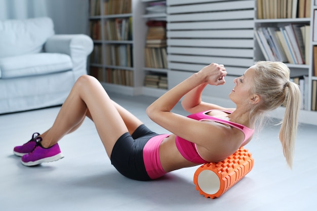 Ejercicios de entrenamiento de mujer rubia con rodillo de espuma
