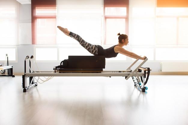 Ejercicios de entrenamiento pilates reformer mujer en el gimnasio interior
