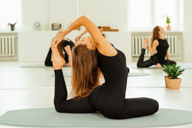 Ejercicios de estiramiento. un grupo de chicas jóvenes con uniformes negros están haciendo ejercicios de estiramiento en el gimnasio.