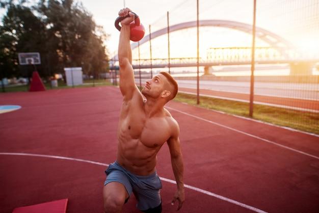 Ejercicios de trabajo de hombre guapo temprano en la mañana con amanecer. entrenamiento físico al aire libre.
