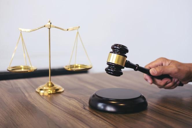 El abogado o el juez de sexo masculino que trabaja con los libros de la ley, mazo, divulga el caso en la tabla en moderno apagado