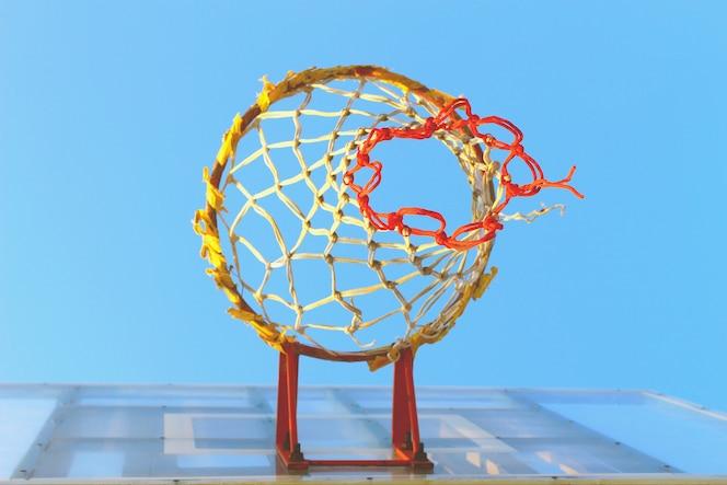 El aro de baloncesto con cielo azul de la vista de gusano, enfoque selectivo