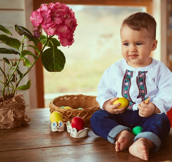 El bebé pequeño tiene un huevo amarillo y se sienta en la mesa