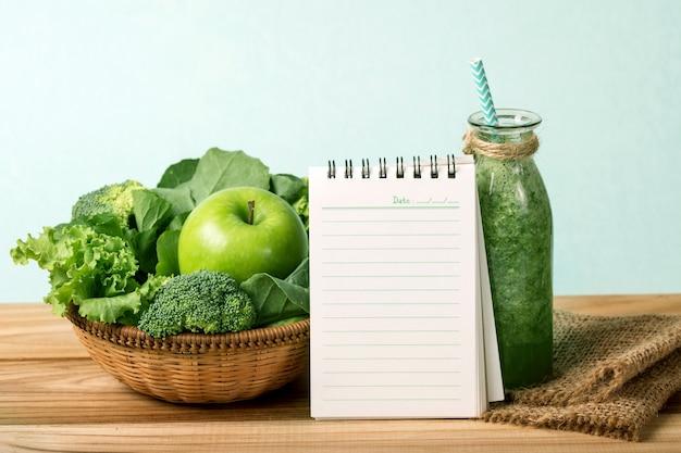 El bloc de notas en blanco y el zumo de batido verde fresco saludable en botella de vidrio en madera