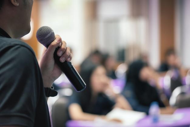 El conferenciante del hombre de cerca habla con el micrófono en foco selectivo.