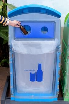 El cubo o la basura con las manos de la niña dejan caer las botellas en la basura reciclable.