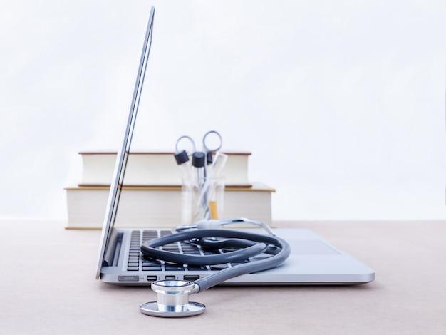 El escritorio del doctor con la computadora y el libro de texto médico con la profundidad del campo baja.