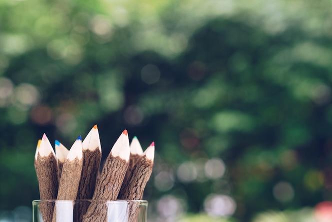 El grupo de lápices de colores de madera en el recipiente glassess con hermoso bokeh natural bac