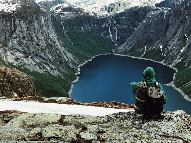 El hombre con una mochila admira el paisaje de montaña magnífico