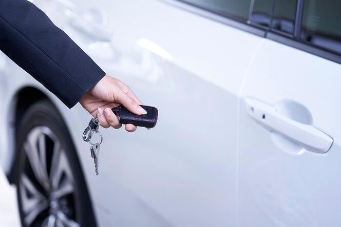 El hombre de negocios abre la puerta del coche con control remoto.