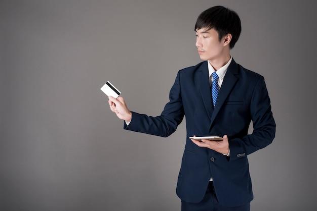 El hombre de negocios está sosteniendo la tarjeta de crédito y la tableta, haciendo compras en línea concepto