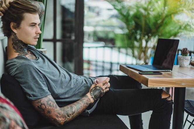 El hombre está trabajando en un café. concepto de trabajo independiente, café y computadora portátil