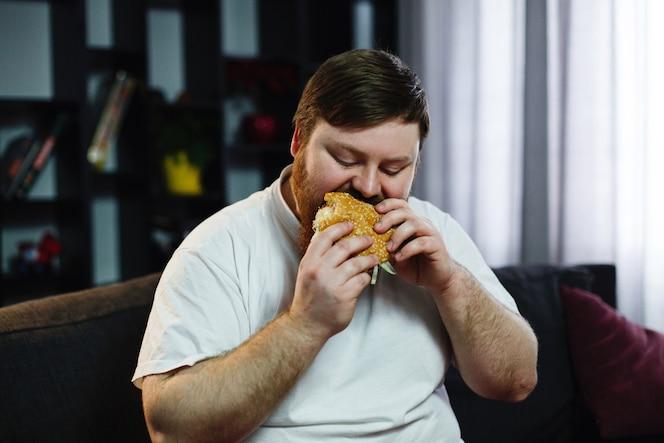 El hombre gordo sonriente come la hamburguesa que se sienta antes de un televisor