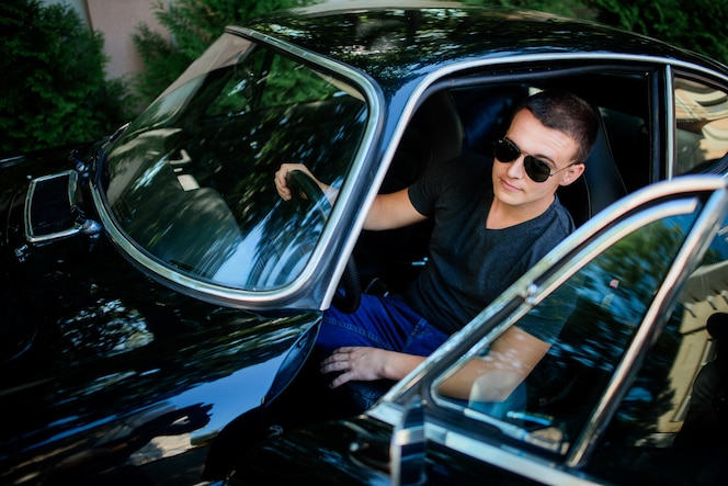 El hombre joven confidente en gafas de sol se sienta dentro de un coche retro del deporte negro