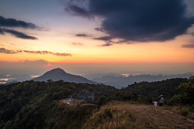 El hombre se para en la montaña superior y toma la foto de la montaña