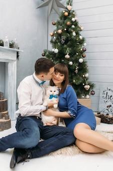 El hombre y la mujer se abrazan posando con gatito blanco delante de un árbol de navidad