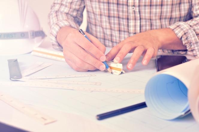 El ingeniero está trabajando en el escritorio con el plan de dibujo