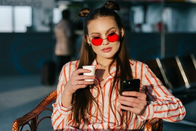 El modelo de moda bonito trabaja con su teléfono inteligente sentado en el café en los rayos del sol