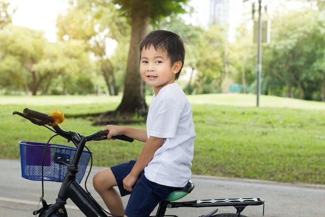 El muchacho lindo asiático monta una bicicleta en el fondo de la naturaleza del parque verde