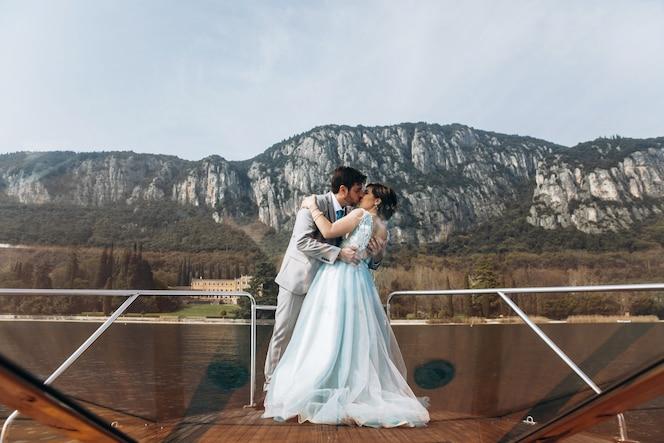 El novio besa a la oferta tímida de la novia en el barco sobre el lago