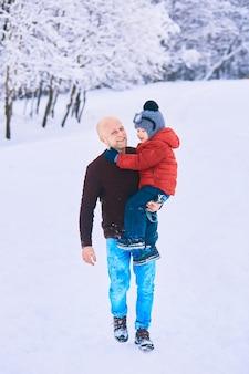El padre sostiene en las manos a su hijo