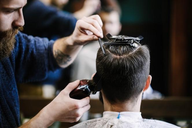 El peluquero corta el pelo del hombre con la podadora y el cepillo