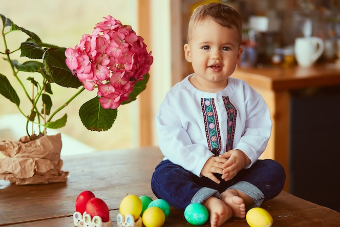 El pequeño bebé se sienta cerca de los huevos de pascua