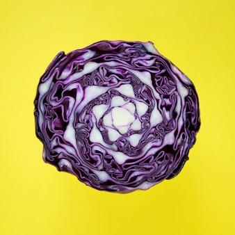 El primer de la col redonda púrpura cortó por la mitad en un fondo amarillo