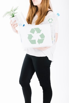 El primer de la mujer que sostiene recicla el cajón de los desperdicios en el fondo blanco