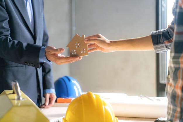 El trabajo de éxito del agente de bienes raíces para transferir el proyecto de construcción terminado al comprador de la casa