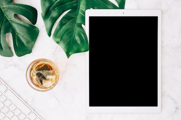 Elaboración de bebidas calientes con bolsa de té en vaso; hojas de monstera; teclado y tableta digital en escritorio blanco.