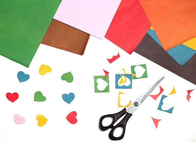 Elaboración de corazones de proyectos con tijeras y papel de construcción colorido