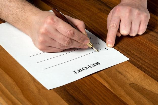 Elaboración de informe en un entorno de trabajo en el escritorio. primer plano de las manos del hombre llenando el espacio en blanco con lápiz