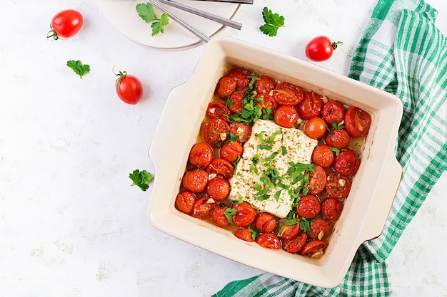 Elaboración de ingredientes para fetapasta. receta de pasta horneada con queso feta de tendencia hecha con tomates cherry, queso feta, ajo y hierbas. vista superior, arriba, copie el espacio.