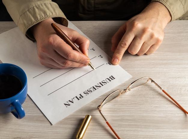 Elaboración de plan de negocios en un entorno de trabajo en el escritorio. primer plano de las manos del hombre llenando el espacio en blanco con lápiz