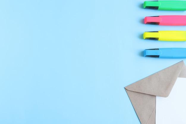 Elabore un conver con una hoja de papel blanca y marcadores multicolores sobre un fondo azul con un espacio de copia