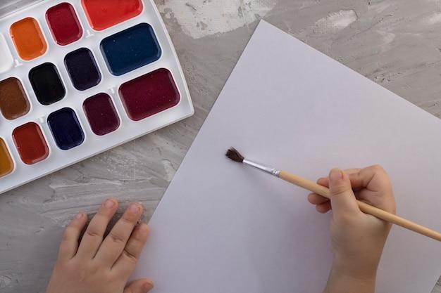 Elección de colores para la primera pintura: primer plano de cubos de pintura con pincel y mano para niños, vista superior