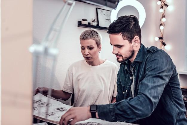 Elección del diseño del tatuaje. cliente guapo con barba en chaqueta de jeans sentado con maestro de tatuajes en el área de la oficina