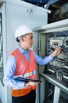 Electricista asiático en el panel en sitio de construcción