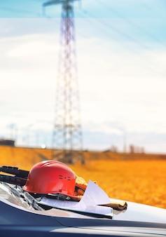 Un electricista en los campos cerca de la línea de transmisión de energía. el electricista gestiona el proceso de instalación de líneas eléctricas. el mecánico con un casco y unos guantes especiales reflectantes en el trabajo.