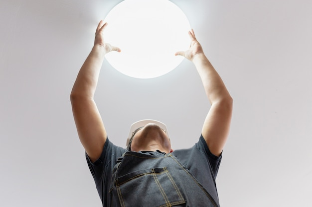 Electricista con casco blanco comprobando la iluminación hasta el techo en el hogar, concepto técnico.