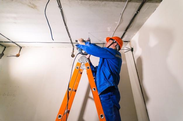 Electricista en casco y uniforme, de pie en la escalera y trabajando con taladro percutor