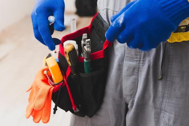 Electricista con herramientas en la correa