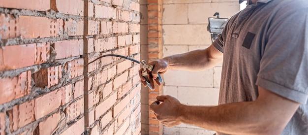 Un electricista de la construcción corta un cable de voltaje durante una reparación