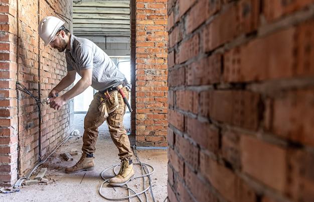 Un electricista de la construcción corta un cable de voltaje durante una reparación.