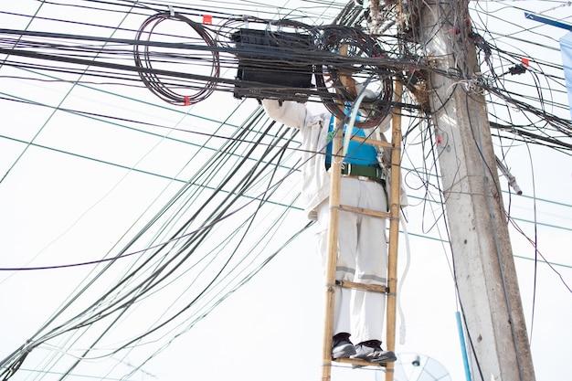 Electricista escalado comprobar cable servicio mantenimiento electricidad poste